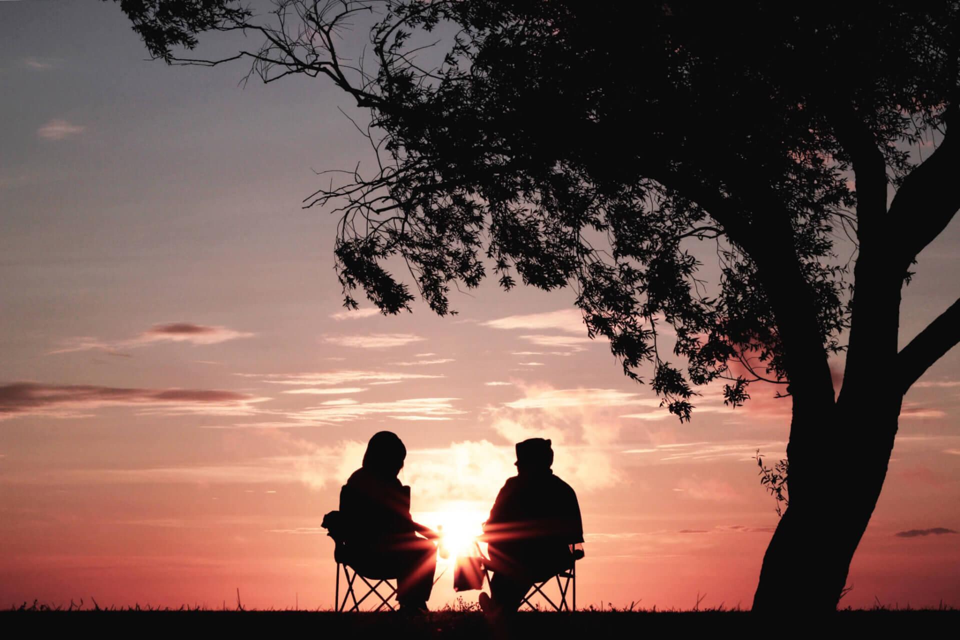 2 people talking under a tree